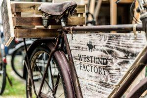 Ein Werbeschild aus Holz im Fahrradrahmen