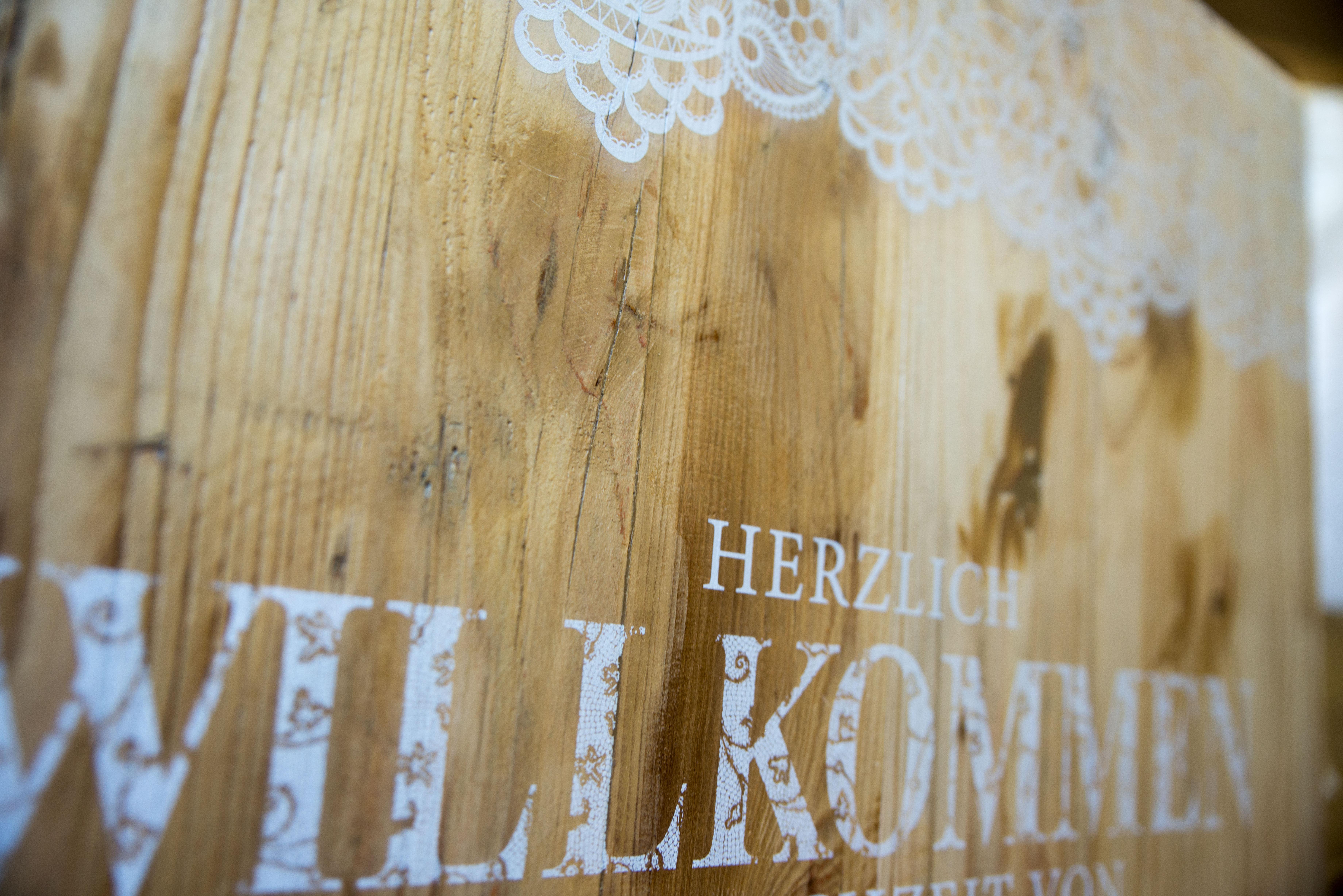 Ein Schild für eine Hochzeit in Weiß direkt auf das Holz gedruckt.