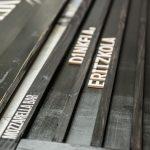 Holztafel mit konturgefrästen Buchstaben
