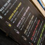 Preistafel, gedruckt auf dunklem Holz