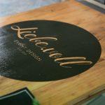 Ein Türschild für ein Geschäft, bedruckt auf Holz